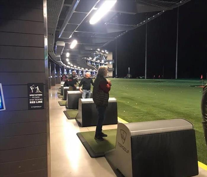 employees golfing in a row