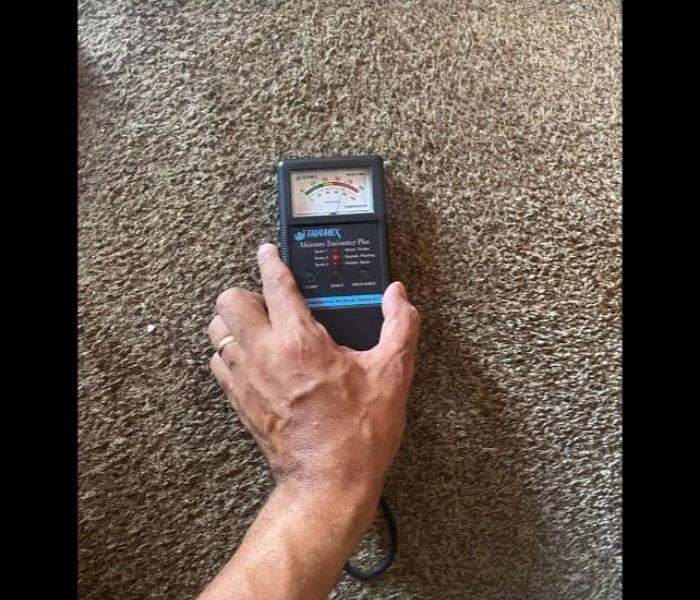 water damaged carpet with moisture meter
